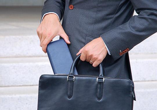 長財布を鞄に入れる男性