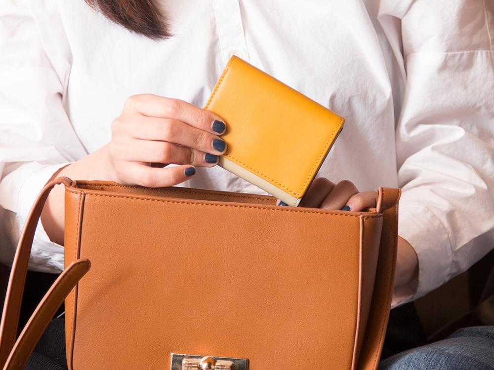 カバンから取り出される3つ折りミニ財布