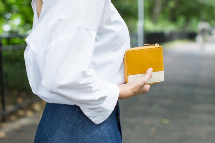 ラウンド2つ折り財布(バイカラー)を手に取り外を歩いている女性